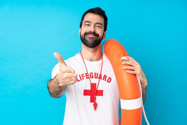 Hombre salvavidas estrechándole la mano por cerrar un buen trato