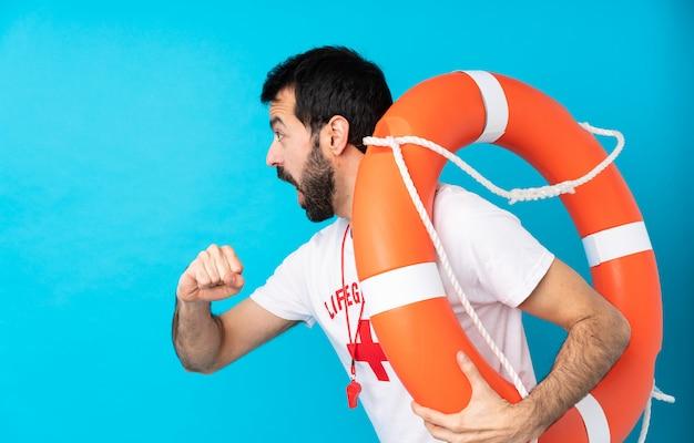 Hombre salvavidas sobre pared azul aislada