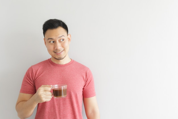 El hombre sano feliz en camiseta roja bebe el café o la bebida asiática de las hierbas.