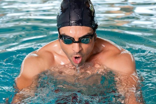 Hombre sano nadando con esfuerzo en la piscina