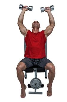 Hombre sano que levanta pesas de gimnasia mientras que se sienta en la prensa de banco