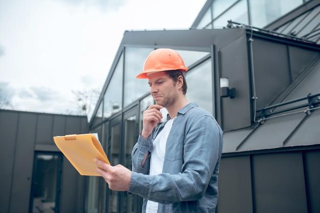 Hombre satisfecho en casco de seguridad mirando plan de construcción