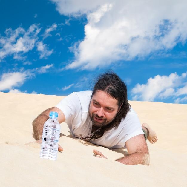 Hombre sediento en el desierto alcanza el agua