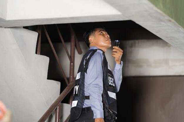 Hombre de seguridad permanente al aire libre con linterna en el edificio