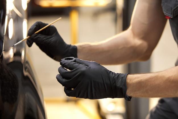Hombre seguro mecánico de automóviles con pincel para pintar un coche