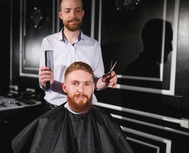 Hombre seguro visitando estilista en peluquería.