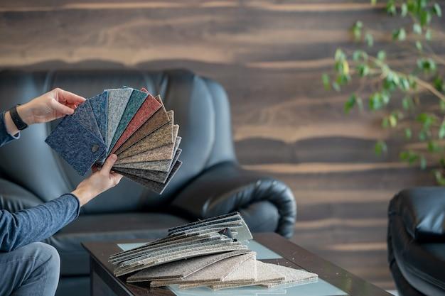 El hombre selecciona una nueva funda para el sofá de la muestra de tarjetas de colores.