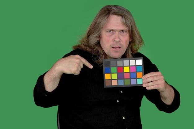 El hombre señala con el dedo el comprobador de color en sus manos.