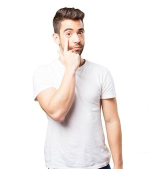 Hombre señalando un ojo a si mismo con un dedo
