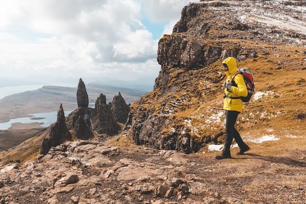 Hombre de senderismo en escocia, isla de skye en el viejo hombre de storr