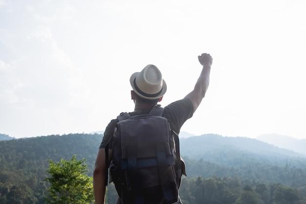 Hombre de senderismo en las montañas al atardecer con mochila pesada