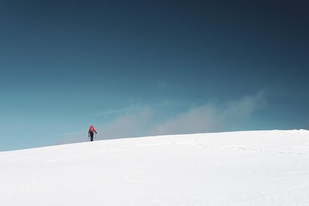 Hombre senderismo en las montañas cubiertas de nieve