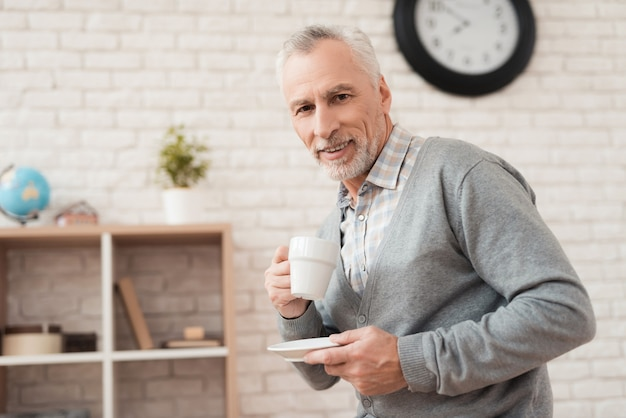 Hombre senior alegre bebiendo café en casa.