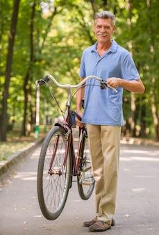 Hombre senior alegre con bicicleta en el parque.
