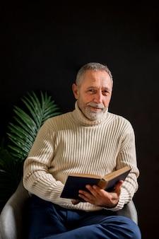 Hombre senior alegre con libro