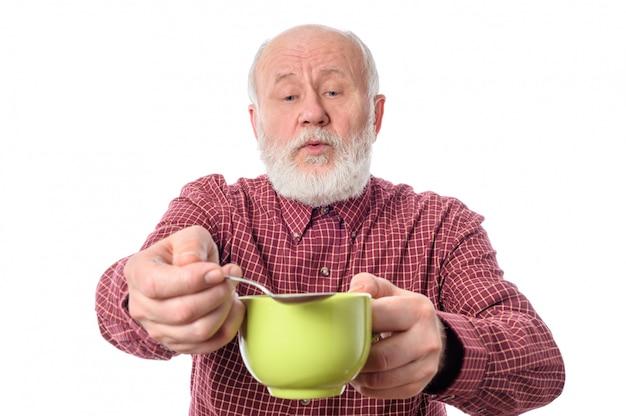 Hombre senior alegre con taza verde y cucharadita.