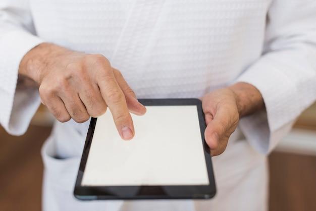 Hombre senior de alto ángulo mirando en una tableta vacía