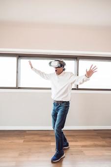 Hombre senior asombrado tocando en el aire durante la experiencia vr