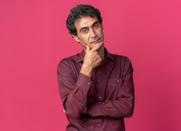 Hombre senior en camisa púrpura mirando a la cámara perplejo de pie sobre fondo de color rosa