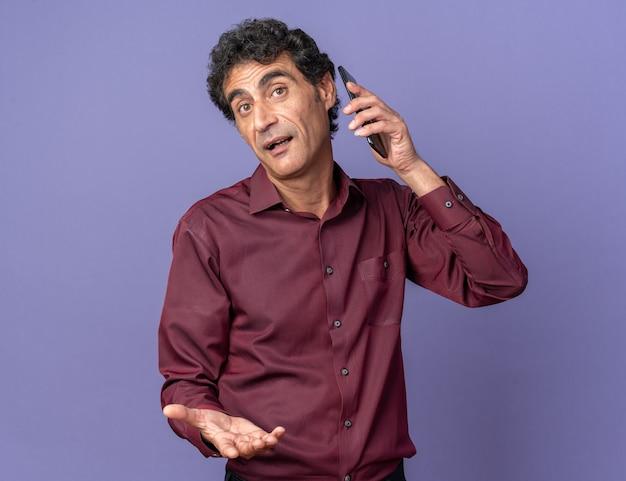 Hombre senior en camisa púrpura mirando confundido mientras habla por teléfono móvil de pie sobre fondo azul.