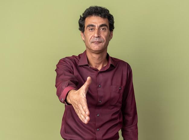 Hombre senior en camisa púrpura ofreciendo gesto de saludo del brazo mirando confiado de pie sobre fondo verde
