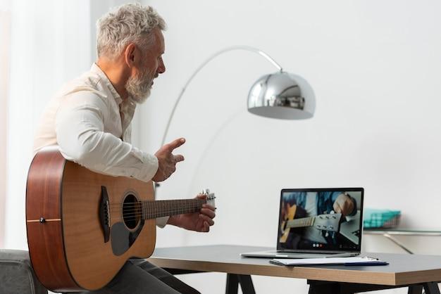 Hombre senior en casa estudiando lecciones de guitarra en portátil