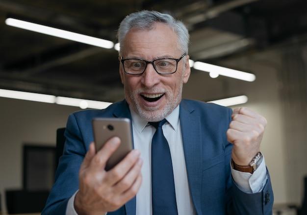 Hombre senior emocionado con teléfono inteligente jugando juegos para móviles