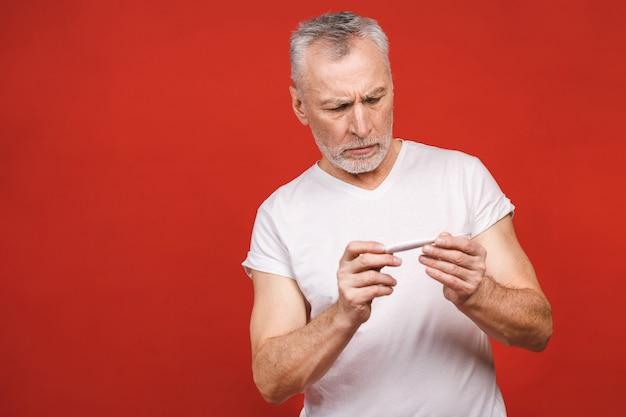 Hombre senior enfermo con termómetro con gripe, alergia, gérmenes, resfriado.
