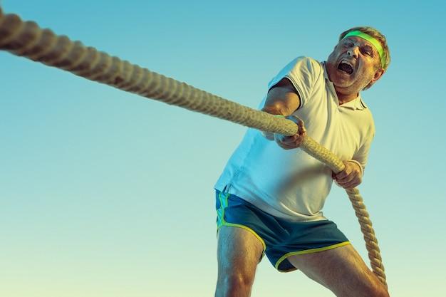 Hombre senior entrenando con cuerdas en pared degradada en luz de neón