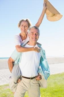 Hombre senior feliz dando a su compañero una alcancía