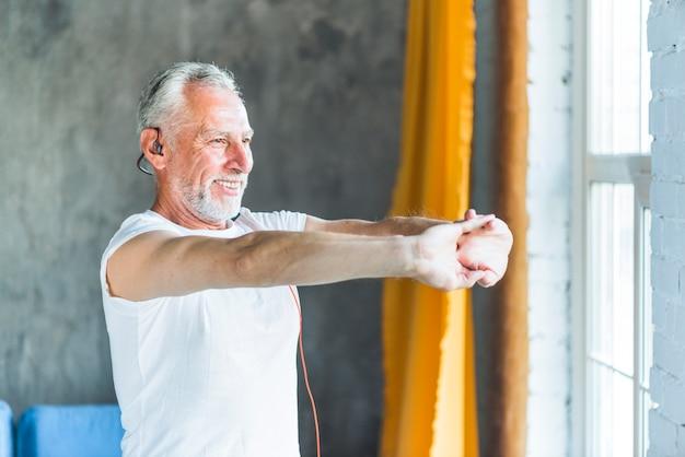 Hombre senior feliz estirando su mano mientras hace ejercicio