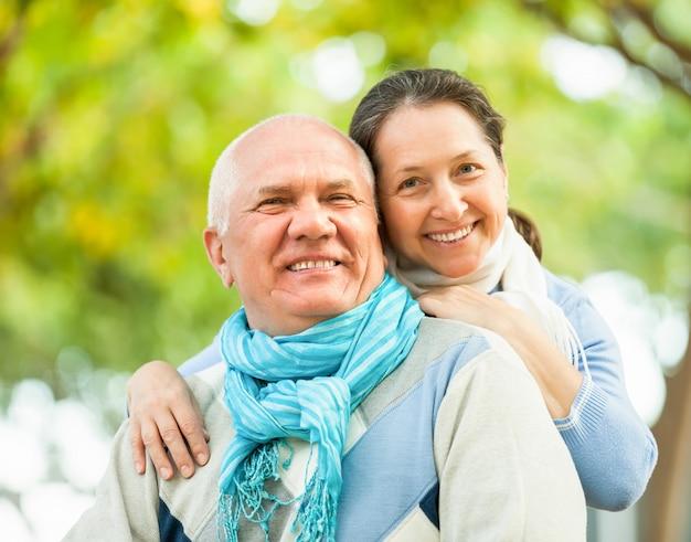 Hombre senior feliz y mujer madura contra el bosque