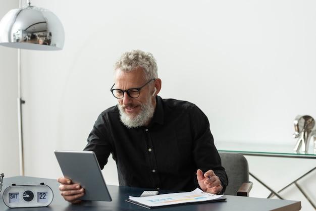 Hombre senior con gafas en casa estudiando mientras usa tableta