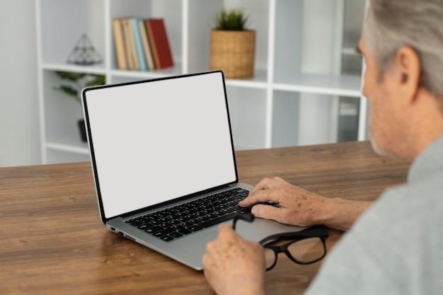 Hombre senior haciendo clases en línea en un portátil.