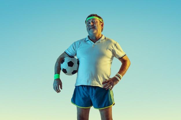 Hombre senior jugando al fútbol en ropa deportiva sobre fondo degradado y luz de neón