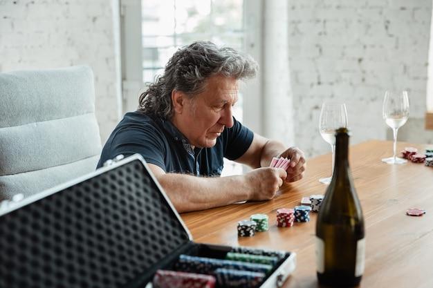 Hombre senior jugando a las cartas y bebiendo vino con amigos