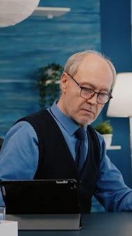 Hombre senior con laptop y tableta al mismo tiempo