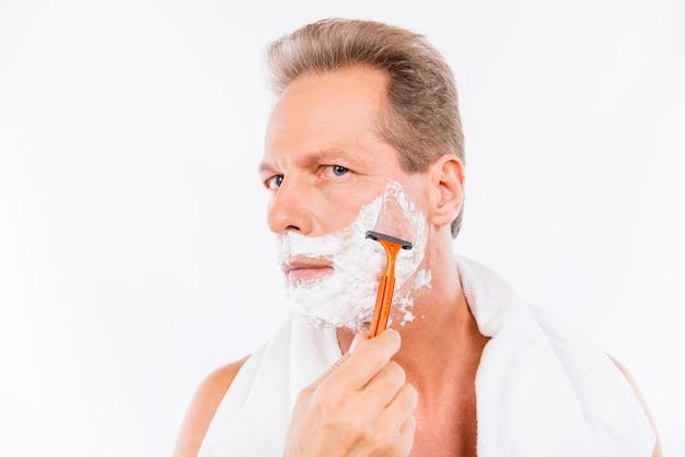 Hombre senior maduro afeitado con navaja delante de cámara