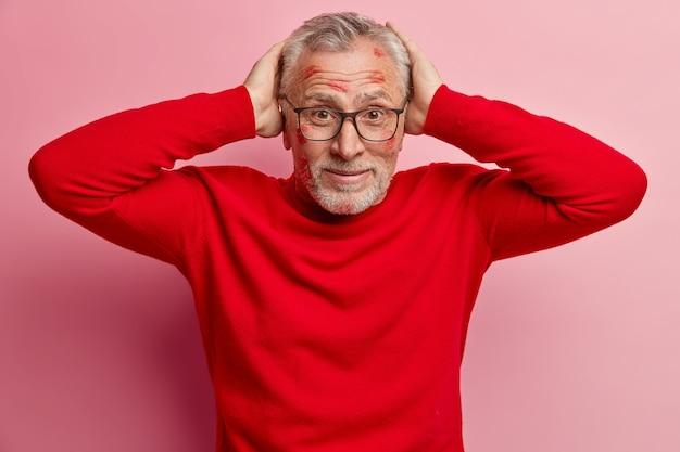 Hombre senior con manchas de lápiz labial en la cara y vistiendo un suéter rojo