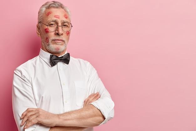 Hombre senior con manchas de lápiz labial en la cara
