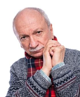 Hombre senior pensativo posando en estudio sobre fondo blanco.