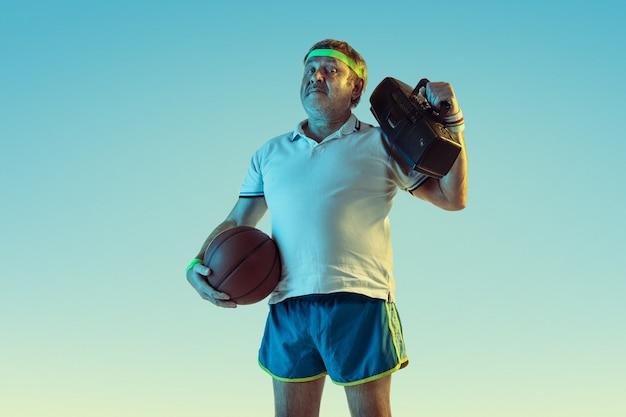 Hombre senior posando impresionante en ropa deportiva con grabadora retro en pared degradada, neón. modelo masculino caucásico en gran forma, deportivo. concepto de deporte, actividad, movimiento, estilo de vida saludable.
