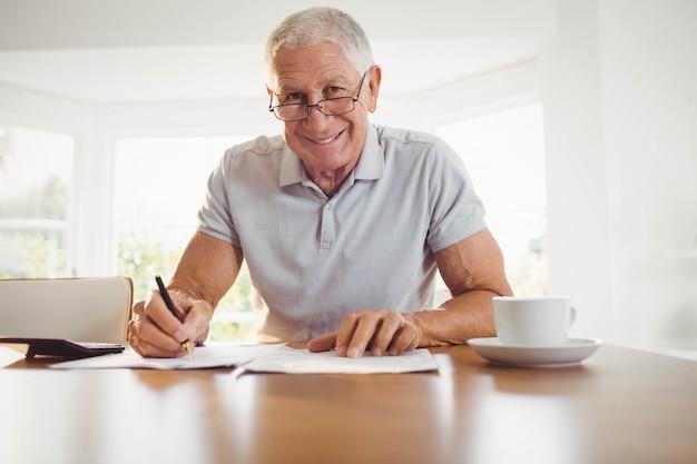 Hombre senior preocupado con documentos fiscales en casa
