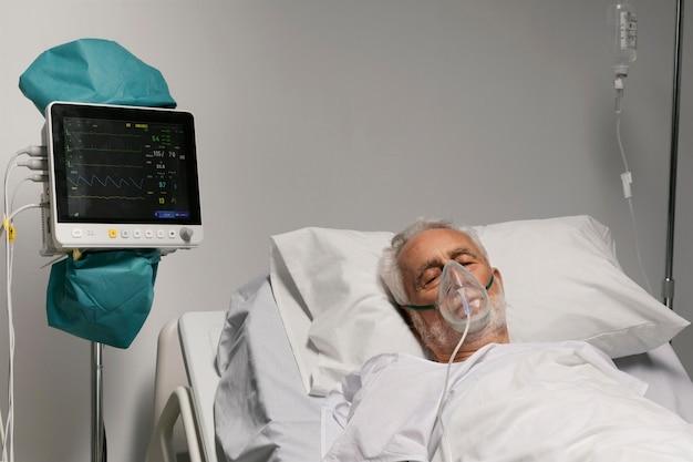 Hombre senior respirando con un equipo especial en el hospital