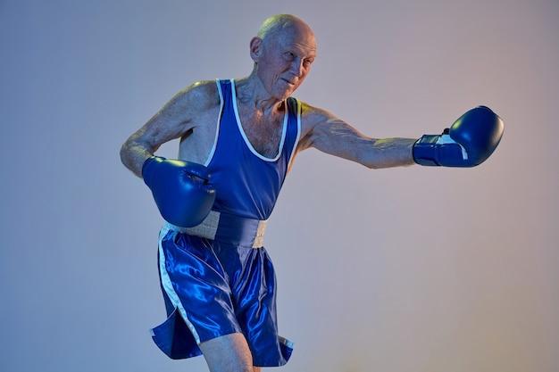 Hombre senior con ropa deportiva de boxeo aislado en la pared del estudio degradado