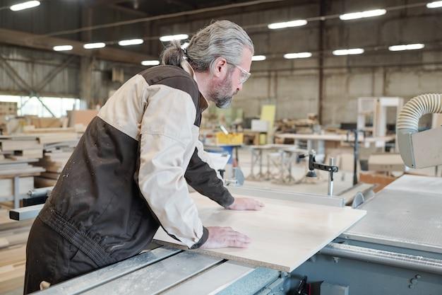Hombre senior en ropa de trabajo de pie junto a una gran máquina de procesamiento industrial y se inclina sobre la tabla de madera mientras va a cortarla