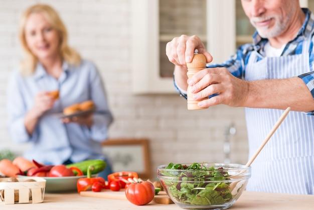 Hombre senior sazonando la ensalada de verduras verdes y su esposa sosteniendo los muffins en la mano en el fondo
