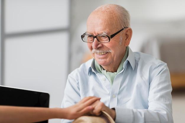 Hombre senior sonriente conversando con la enfermera