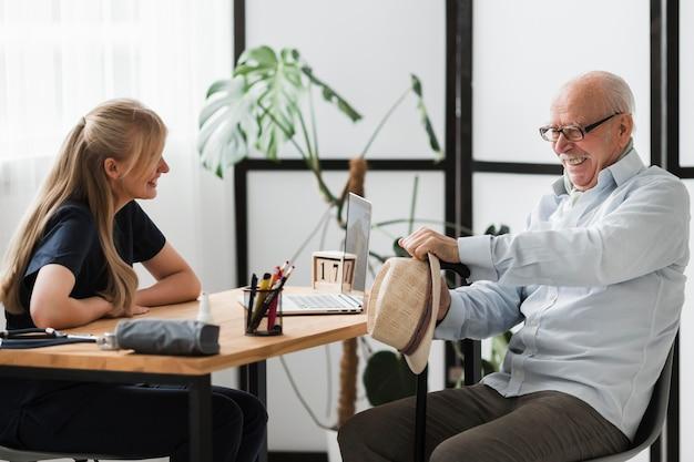 Hombre senior sonriente en un hogar de ancianos con enfermera