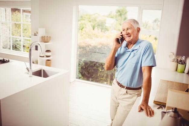 Hombre senior sonriente en una llamada telefónica en la cocina